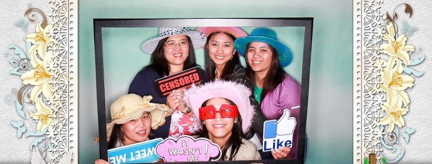 Ladies wearing hats and holding photo booth signs