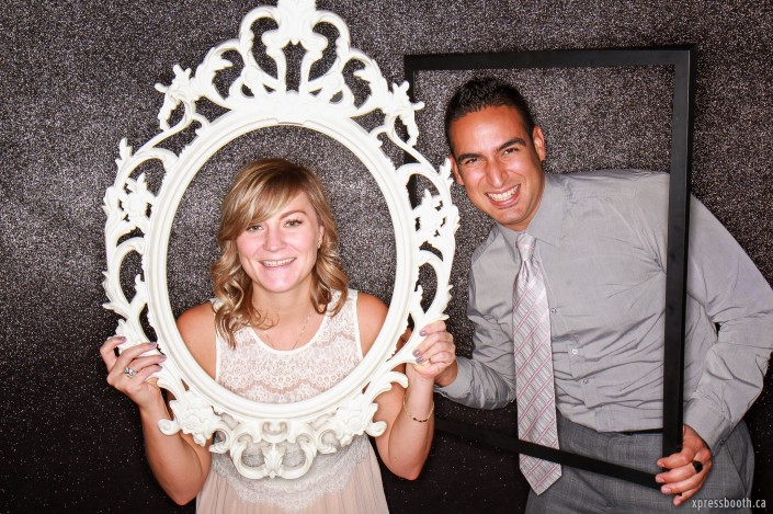 Sweet couple having fun in the photobooth and playing with picture frames