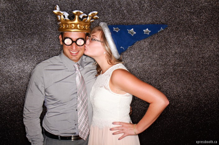 Kissing couple wearing wizard hat, crown and bottle glasses