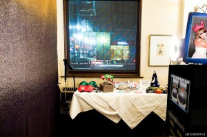 View looking out into the street from Teatro Restaurant, with the black and silver glitter backdrop and photo booth prop table