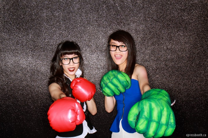 Two girls taking a photo in the photo booth wearing boxing and hulk gloves