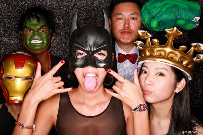 A group of people posing in the booth wearing superhero masks